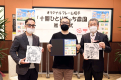 フレーム切手を手にする横山さん(中)と横山さんから贈られた色紙を手にする高橋社長(左)と沼袋統括局長(右)