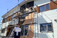 改修が進む建物を前に、ゲストハウスの完成パースを手にする小松さん
