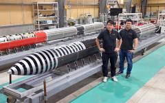 公開された改良版モモの前に立つ(右から)稲川社長、堀江氏(IST工場内で。小山田竜士撮影)