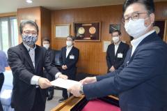 按田町長(右)から辞令を受け取る大崎氏
