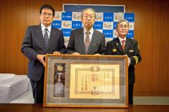 勲記と勲章が伝達された小椋さん(中央)。左は村瀬町長、右は川津町消防団長