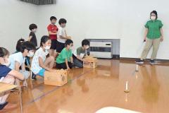 空気砲の実験を楽しむ児童。右は内山指導員
