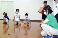 空気砲の威力を確かめる児童。手前右は内山指導員