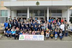 校舎の玄関前で記念撮影する全校児童と地域住民ら
