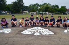 グラウンドに刻まれた校章を囲んで記念撮影する全校児童