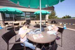 屋外のさわやかな風を感じながら読書する子どもたち