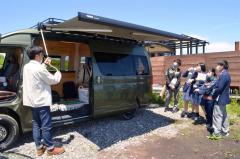 吉岡さん(左)から宿泊できるレンタカーの説明を受ける大樹高生