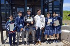 吉岡さん(右から3人目)と笑顔で写真に収まる大樹高生