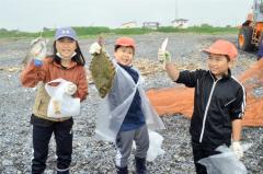 水揚げされた魚を手にする子どもたち