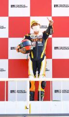 今季1勝目を飾った小林崇晶が表彰台の中央でポーズを取る