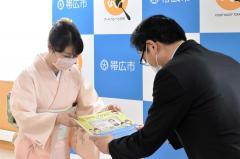 加藤会長(左)が米沢市長(右)に絵本を手渡した