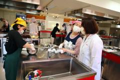 調理実習中、遠藤校長(右)に質問する参加者(右から2人目)