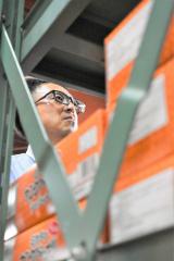 数千にもなる段ボールが積まれた倉庫内で在庫を整理する渡鍋さん