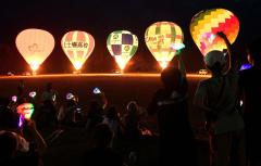 上士幌小6年生の声援に合わせてバーナーに点火する町内5団体の熱気球(21日午後7時45分ごろ、上士幌小学校の校庭で。塩原真撮影)