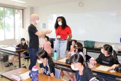 子どもたちに英語を教える講師のピナールさん(中央左)とロビンソンさん(中央右)