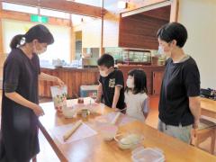 千裕さん(左)に教わりピザづくりを体験する親子
