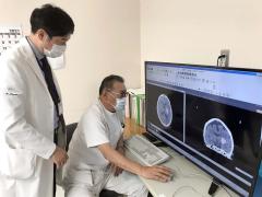 CT画像が写ったモニターを見る(右から)西尾副院長、井上部長