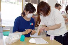 井川さん(右)の指導を受け、ちあぱい作りに挑戦する参加者
