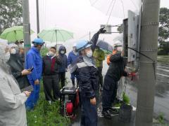 雨の中、停電を想定して発電機をつないで信号機の復旧訓練を行う参加者
