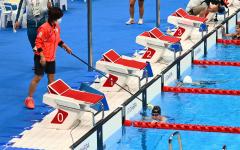 レース後、タッパー(左)の誘導でプールから引き揚げる小野智華子(金野和彦撮影)
