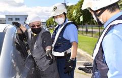 犯人のポケットから包丁を取り出す池田署員(8月31日、池田町西部地域コミュニティセンターで)