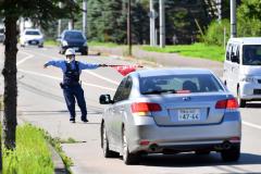 犯人役が乗った車を止める帯広署員(8月31日、十勝川温泉駐在所前で)