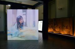 齋藤飛鳥さんのパフォーマンス映像と「花下遊楽図屏風」(東京国立博物館所蔵。本展覧会では複製を展示。右隻中央は原品では消失。複製は、ガラス乾板の画像から復元し合成した)  *作品名の後のクレジットは必須です