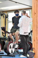 デニスコーチ(右)のアドバイスを聞きながらサイクリングトレーニングを行う村上右磨
