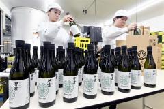 自らが醸造に関わった日本酒を箱詰めする(左から)帯広畜産大学4年生の高山さんと酒井さん(21日午前10時半ごろ、塩原真撮影)