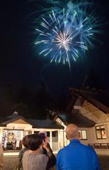 秋の夜空を彩ったサプライズ花火を楽しむ見物客ら(22日午後7時ごろ、小山田竜士撮影、2・5秒露光)