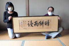 渋沢栄一が揮毫した書「晴耕雨読」を紹介する山本さん夫妻