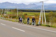遠くヌプカの里を望みながら自転車で疾走する参加者(先頭は小林町長)
