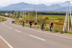 遠くヌプカの里を望みながら自転車で疾走する参加者