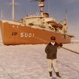 南極観測船「ふじ」をバックにして写真に納まる佐藤さん