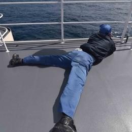 揺れる船上で射撃姿勢を取り初氷山を撮る自衛隊員