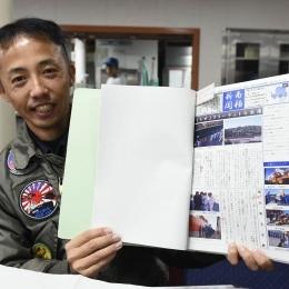 南極新聞をアピールする松久保成人飛行士。題字がどこかの新聞社に似ているような。