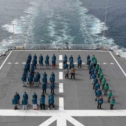 南極観測船「しらせ」の飛行甲板上で57の人文字を作る隊員と同行者
