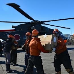 ヘリコプターから第一便物資を手渡しで搬出する隊員