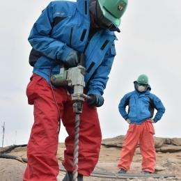 ドリルで岩盤を掘る調理の長谷川隊員(左)と同行者の渡辺さん(2015/12/28)