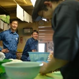 伊澤さんの包丁さばきを見るしらせ当直の菱沼正樹さんと塚本一光さん(左から)