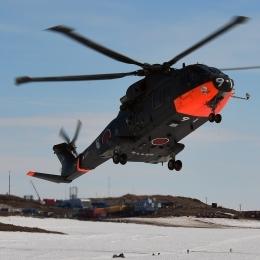 燃料などの物資を運ぶヘリコプター。奥は昭和基地(日本時間1月14日午後8時ごろ、しらせ甲板上から撮影)