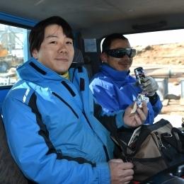 休憩中にトラックの中でおやつを頬張る久保田寛丈隊員と同行者の須藤健司さん(左から)