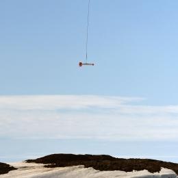 観測機器をつって海氷上を飛ぶヘリコプター(1月10日)