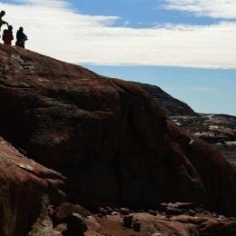 岩の上から岩石採取する場所を探す隊員ら(1月24日)