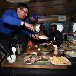雪上車で食事を取る隊員