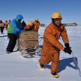 掘削した氷をヘリコプターに運び入れる隊員ら