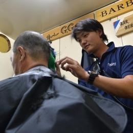 後藤隊員の髪を刈る石川隊員