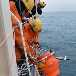 浮上した海底圧力計を船内に回収する自衛隊員