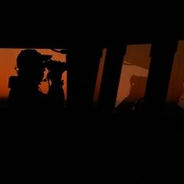艦橋で双眼鏡をのぞき氷山の位置を確認する自衛官(現地時間2月17日午後8時50分)