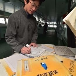 艦橋で当直記録を写す柴田さん(2月20日撮影)